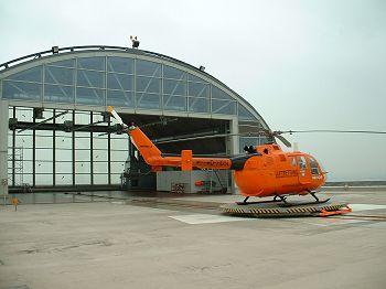 Vrtulník na samohybné plošině před hangárem na střeše úrazové nemocnicne